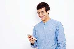 Guy texting on mobile phone. Young hispanic man wearing jeans shirt and glasses reading something funny from his smartphone and laughing against white wall Royalty Free Stock Image