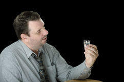 Guy thinks to drink one more vodka shot. Mature guy thinks to drink one more vodka shot Royalty Free Stock Photo