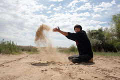 The guy throws sand. Man sitting on the nature  and throwing sand Royalty Free Stock Images