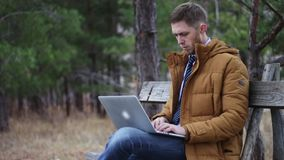 The guy in a tie and jacket is sitting with a laptop on a bench in an autumn park. typing text on the keyboard, surf stock video