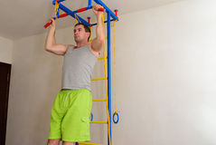 Guy to catch up on the bar wide grip. The man pulled on the wall bars royalty free stock image