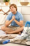 Guy torubled of housework. Young guy sitting on living room floor looking up troubled about housework, surrounded by laundry Stock Photography