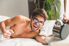 Guy touching alarm-clock and bawling with anger Stock Photos