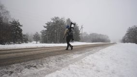 The guy with the tourist backpack goes on a foggy winter day. Danger on the road in winter,. The guy with the tourist backpack goes on a foggy winter day. Danger stock footage