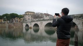 Guy tourist films old bridge reflecting in river stock footage
