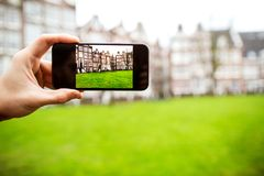 Guy tourist holding a phone, photographing a building in Amsterd. Am, close-up Stock Images