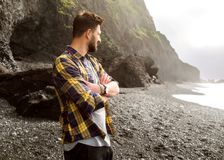 Guy tourist standing on the beach at sunset in Iceland in checke. Red shirt Stock Photos