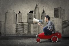 Guy on a toy car screaming in a megaphone Stock Photography