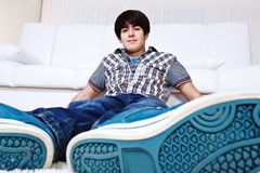 Guy in trainers. Teenage guy in trainers sitting in front of the sofa Stock Image
