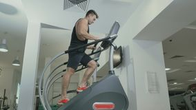 Guy training legs moving up stairs in the gym. Muscular sportive man has a sport exercises in the gym. Handsome guy is moving up stairs and looks forward. Young stock video footage