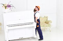 Guy from transportation company moving old piano alone. Tired guy lifting heavy stuff. Bearded man from transportation company moving old piano alone. Tired guy stock image