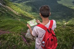 Man with red backpack lost in mountains, holding trip map, paves tourist route. Summer royalty free stock photography