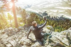 Guy traveler takes pictures of self on a smartphone in the background of mountains. View from back of the tourist royalty free stock image