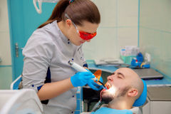 Guy treats his teeth in a dental office at the doctor Stock Photos