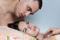 The guy tries to wake the girl with a kiss. Morning awakening Royalty Free Stock Images
