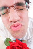 Guy trying to be romantic giving a kiss holding rose Stock Image