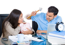 Guy trying to break girl's piggy bank to get money Royalty Free Stock Images
