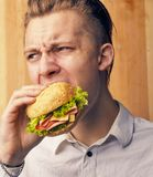 Guy is really trying to burger. The young guy is really trying to burger Stock Images