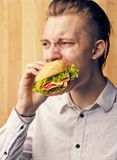 Guy is really trying to burger. The young guy is really trying to burger Stock Photos