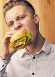 Guy is really trying to burger. The young guy is really trying to burger and looking at camera Stock Photography