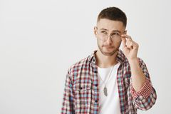 Guy trying to make calculations in mind. Indoor shot of good-looking modern male with beard, wearing and holding eyewear. While looking up with thoughtful Stock Photography