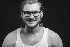 Guy is trying to smile realistic. Guy in white singlet is trying to smile realistic. black and white photo. funny face stock images