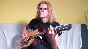 The guy tunes an acoustic guitar on a yellow background. Turns hand chopping strings stock footage