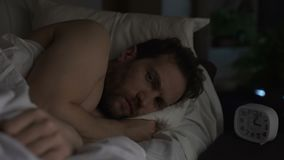 Guy turning in bed unable to fall asleep, looking angrily at clock, insomnia. Stock footage stock footage