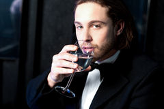 Guy in tuxedo drinking cocktail Stock Photography