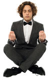 Guy in tuxedo striking a lotus posture Stock Photos