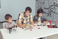 A guy and two boys sit at a large gray table and construct a robot. Before them, many parts and components. Two boys and guys are sitting at a large gray table stock images