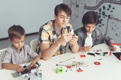 A guy and two boys sit at a large gray table and construct a robot. Before them, many parts and components. Two boys and guys are sitting at a large gray table stock photo