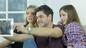 Guy and two girls make selfieie with a tablet. Happy friends have fun together. Cheerful young people sitting on the couch while cuddling fun and make selfieie stock footage