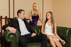 A guy and two girls in the room Stock Photography