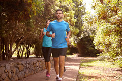 A guy and two girls running Stock Images