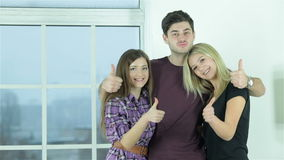 Guy and two girls show thumbs stock video