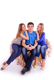 Guy with two girls sitting on the couch Stock Photos
