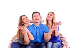 Guy and two girls sitting on the couch and looking up. Isolated Stock Images