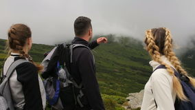 A guy and two traveling girls look at the camera against the background of mountains and fog.  stock footage