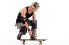 Guy tying his shoes laces and sitting on skateboar stock image