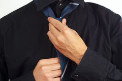Guy tying his tie over black shirt closeup Stock Image