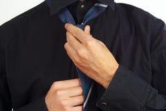 Guy tying his tie over black shirt closeup Stock Image