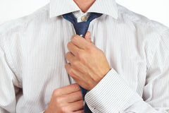 Guy tying his tie over bright shirt closeup Royalty Free Stock Image