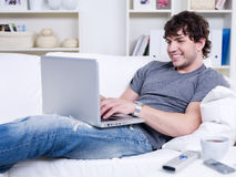 Guy typing on the laptop at home Royalty Free Stock Photos
