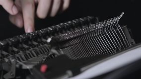 Mechanism of a retro typewriter, fingers print text. Close up. Guy is typing on a retro typewriter a letter to a friend, an old mechanism. Close-up stock video