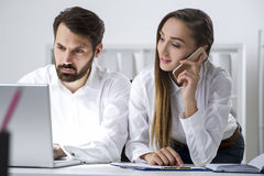 Guy is typing, woman is on her phone in office Royalty Free Stock Image