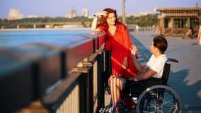 Guy On uma cadeira de rodas e uma menina com cabelo vermelho comunica-se na margem na noite do verão filme