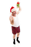 Guy in Underwear Under the Mistletoe. Middle-aged man in his underwear, and a santa hat, holding mistletoe and waiting for a kiss. Full body isolated royalty free stock photography