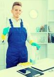 Guy in uniform cleaning in office. Portrait of handsome guy in uniform cleaning in office Stock Photos
