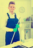 Guy in uniform cleaning in office. Portrait of smiling handsome guy in working overall cleaning in office Stock Images